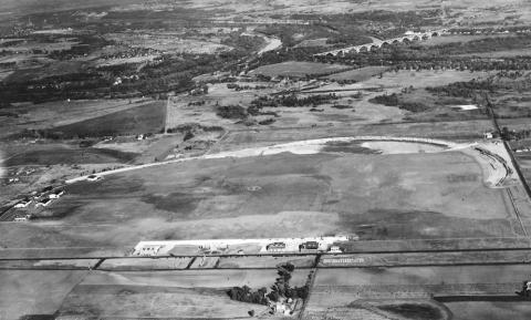 By 1930 the Minneapolis park board had begun the transformation of the old speedway into an airport, but a segment of the old 2-mile oval still remained. The Mendota Bridge is upper right. Note the NWA hangar among the airport buildings. The landing strip was not on the old concrete race track, which was too rough. The landing strip was on the grass in the infield of the old race track. (J. E. Quigley, Minneapolis Park and Recreation Board)