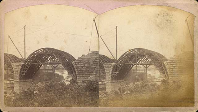 This stereoscope image shows the stone arches being built over forms in 1883. (Henry Farr, Minneapolis Historical Society)