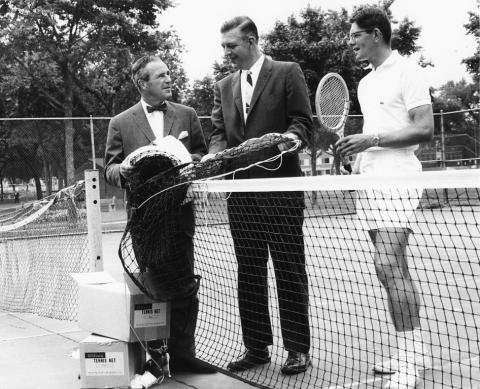 Robert Ruhe, middle, Minneapolis Superintendent of Parks 1966-1978 proposed a tough land policy to defend against the taking of parkland for freeways and other uses. In this 1968 photo he is accepting a gift of 60 tennis nets from General Mills. Before that time, nets were not provided on most city courts. Players had to bring their own. (MPRB)