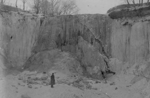 An unknown man staqnds at the foot of Minnehaha Falls in January, 1899. (Photo courtesy Edward Tobin Thompson)