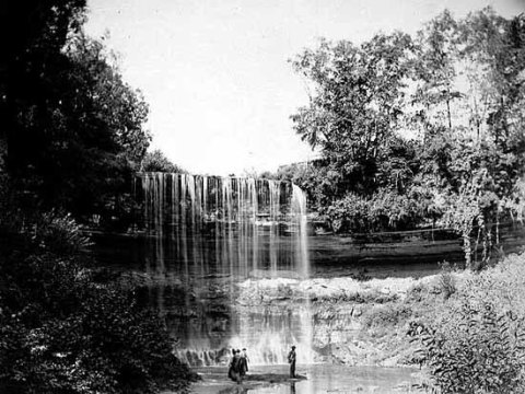 Minnehaha Falls in the 1890s. Notice teh striation sof limestone above sandstone in the cliffs beside the Falls. This was at a time of low water in the falls so the structure of the falls and the gorge are visible.