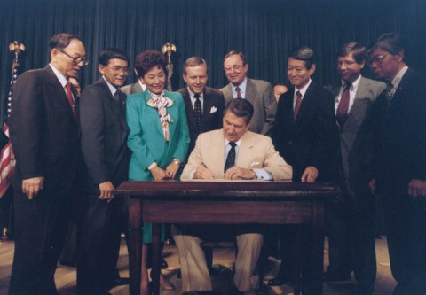Ronald_Reagan_signing_Japanese_reparations_bill 1988